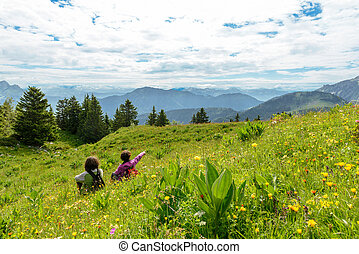 two women sitting in the grass and looking at the landscape