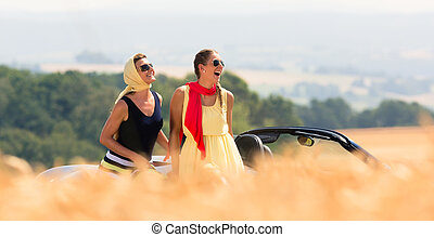Two women sitting on hood of convertible car