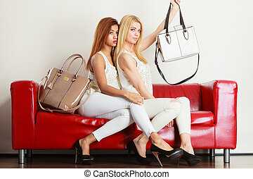 Two women sitting on sofa presenting bags