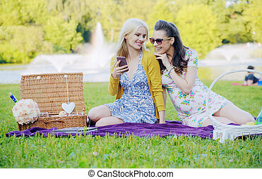 Two women sitting on the blanket and texting - Two women...