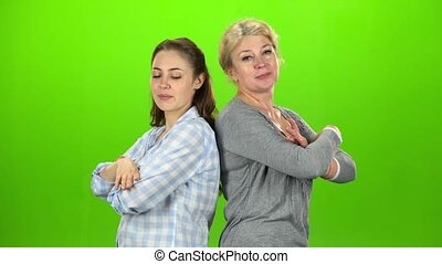 Two women stand back to back and cross their arms. Green...