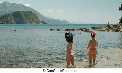 Two women stand in water by seashore on summer day.