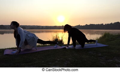 Two Women Stand on Mats And Stretch Out Doing Forward Lunges at Sunset