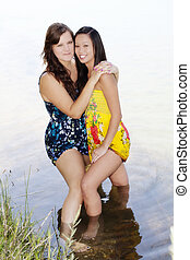 Two Women Standing In Water With Dresses