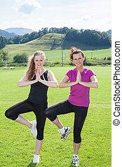 Two Women Standing in Yoga Tree Pose in Field