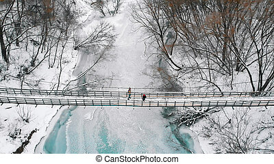 Two women standing on the snowy bridge in the winter forest