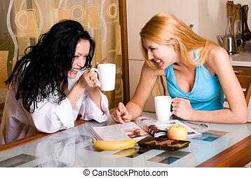 two women - two young beautiful women drink tea in the...