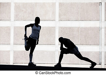 Two women stretching before running.