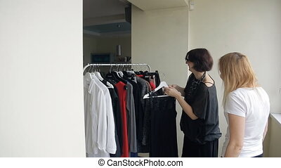 Two women, stylist and client, choose new image in dressing room.