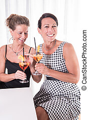 two women talking and having a drink