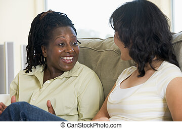 Two women talking in living room and smiling