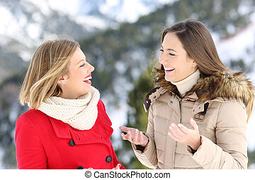 Two women talking in winter holiday in the mountain