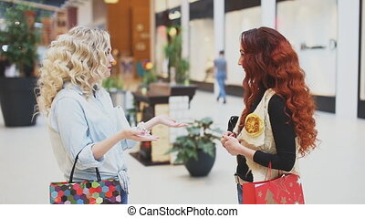 two women talking with shopping bags at the mall
