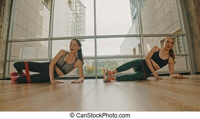 Two women training in the fitness studio - training their legs in the studio using a stretching strap between thighs. Mid shot