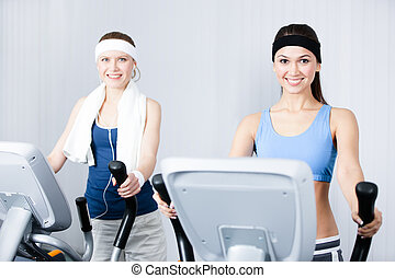 Two women training on training apparatus in gym