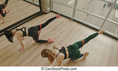 Two women training their legs in the studio using a stretching strap between thighs - standing on the knees and pulling the leg up. Mid shot