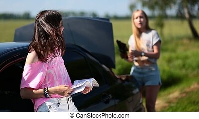 Two women trying to apply jack with user guide - Two young...