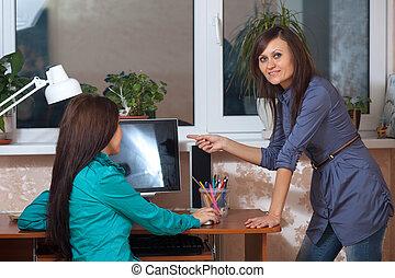 Two women using computer - Two women using computer in...