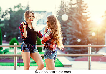Two women vaping outdoor. The evening sunset over the city. ...