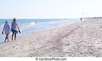 Two women walk along sandy beach in summer