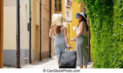 Two women walk along the alley and to their right a green...