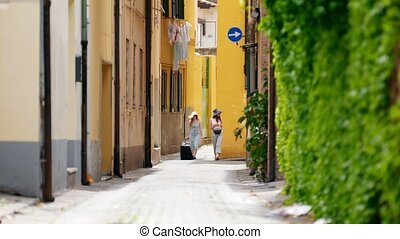 Two women walk between the buildings - Shot from away - a...