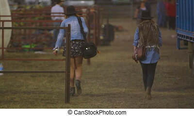 Two women walking in a ranch - A still wide shot of the back...