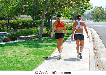 Two Women Walking - Two fit and shapely young women in...