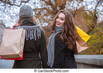 Two women walking with shopping bags outdoors