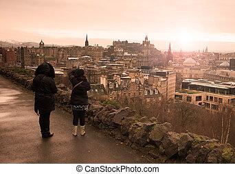 Two women watching the city of Edinburgh