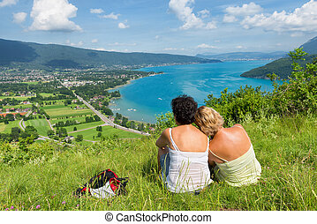 Two women watching view of Lake Annecy - Two women lesbian...