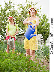 Two women watering vegetables with watering pot