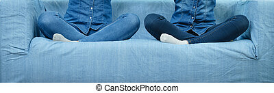 Two women wearing jeans sitting on sofa.