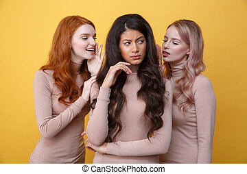 Two women whisper to their friend