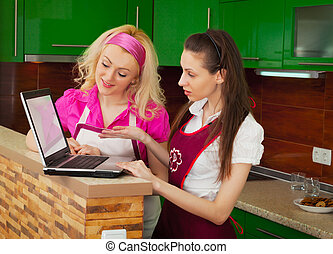 Two women with a laptop looking for a recipe in the Internet