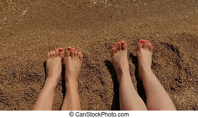 Two women with bare feet sitting on sandy beach in summer.