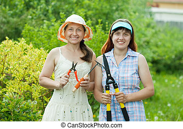 Two women with garden tools