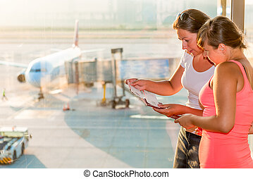 two women with tickets on the background of the aircraft
