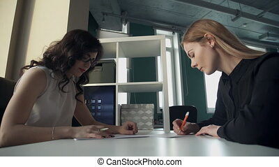 Two women work with some documents, write reports in office.