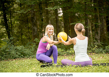 Two women working out exercising in the garden