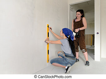 Two women working with a spirit level - Two young women...