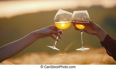 Two women's hands clink glasses on a background of sunset...