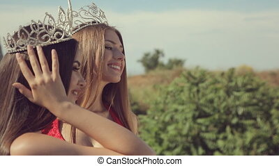 Two wonderful long-haired beauties in crowns standing in the...