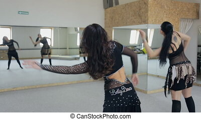 Two wonderful women practice belly dance motions in front of mirror.