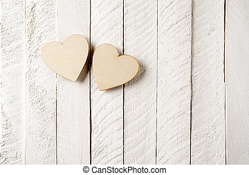 Two wood heart on a vintage wooden background.
