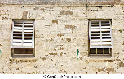 Two Wood Shutters in an Old Stone Block Wall