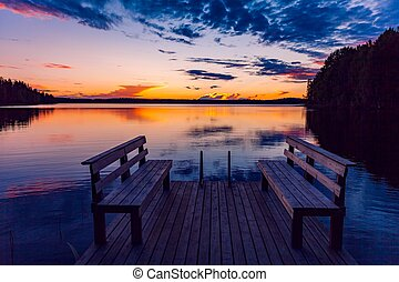 Two wooden bench or chairs on a wood dock facing a lake at sunset in Finland