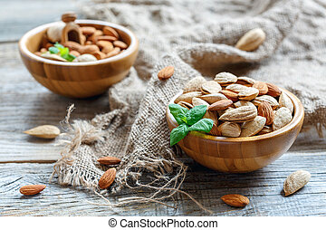 Two wooden bowls with almonds.