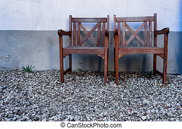 Two wooden chair against a wall with stones on the ground