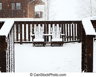 Two wooden chairs connected to each other stand on the terrace covered with snow in winter during a snowfall